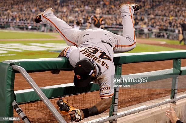 Pablo Sandoval of the San Francisco Giants flips into the Pittsburgh Pirates dugout as he catches a fly ball hit by Russell Martin of the Pittsburgh...