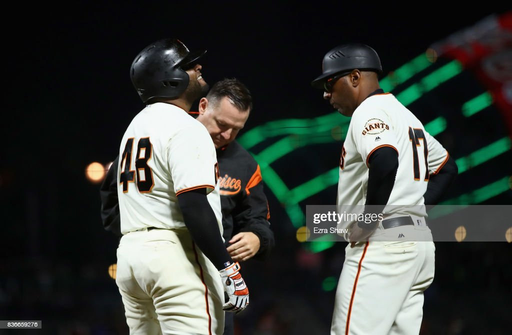 Pablo Sandoval #48 of the San Francisco Giants has his hand examined by the trainer and first base coach Jose Alguacil #17 after being hit by a pitch in the eighth inning against the Milwaukee Brewers at AT&T Park on August 21, 2017 in San Francisco, California.