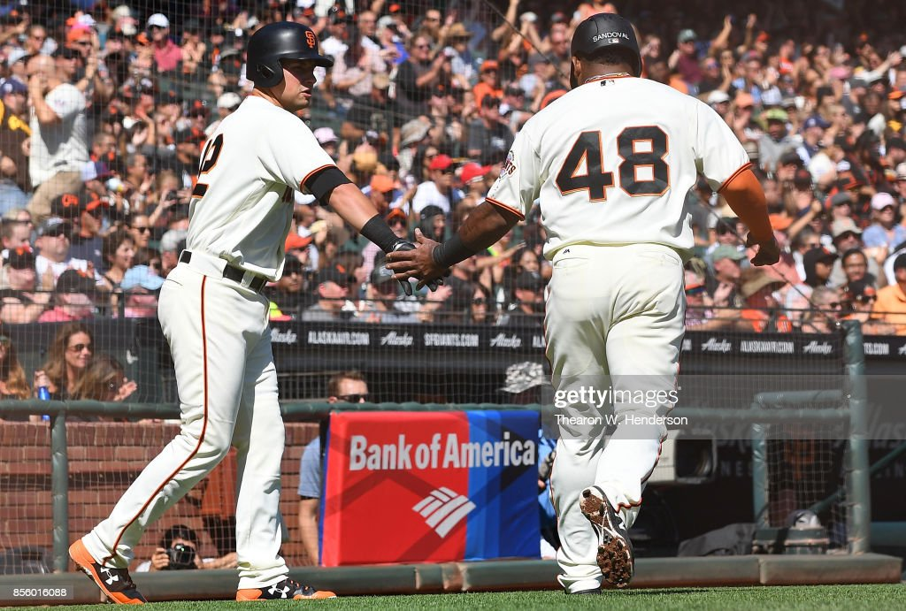Pablo Sandoval #48 of the San Francisco Giants is congratulated by Joe Panik #12 after Sandoval scored against the San Diego Padres in the bottom of the second inning at AT&T Park on September 30, 2017 in San Francisco, California.