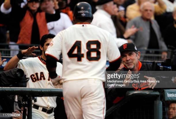 Pablo Sandoval of the San Francisco Giants is greeted by Angel Pagan and manager Bruce Bochy after hitting his first inning home run against the...