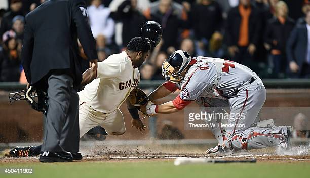 Pablo Sandoval of the San Francisco Giants is tagged out at home plate by catcher Wilson Ramos of the Washington Nationals in the bottom of the sixth...