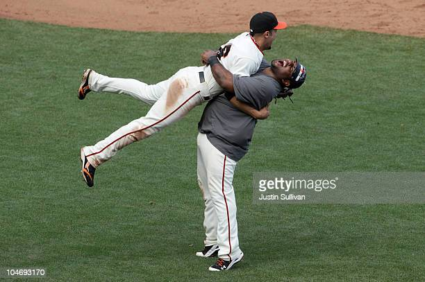 Pablo Sandoval of the San Francisco Giants lifts teammate Andres Torres after they clinched the National League West divsion against the San Diego...
