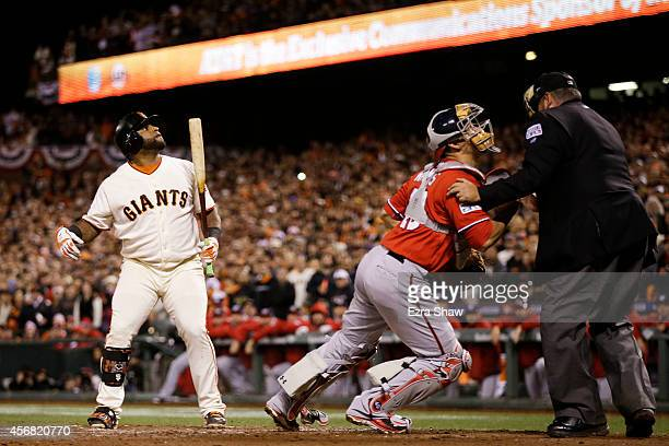 Pablo Sandoval of the San Francisco Giants looks on as Wilson Ramos of the Washington Nationals tries to recover a wild pitch that scored Joe Panik...