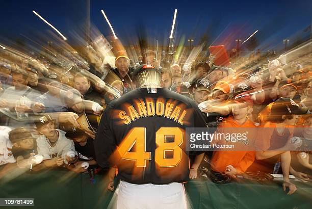 Pablo Sandoval of the San Francisco Giants signs autographs for fans before start of the spring training game against the Los Angeles Dodgers at...