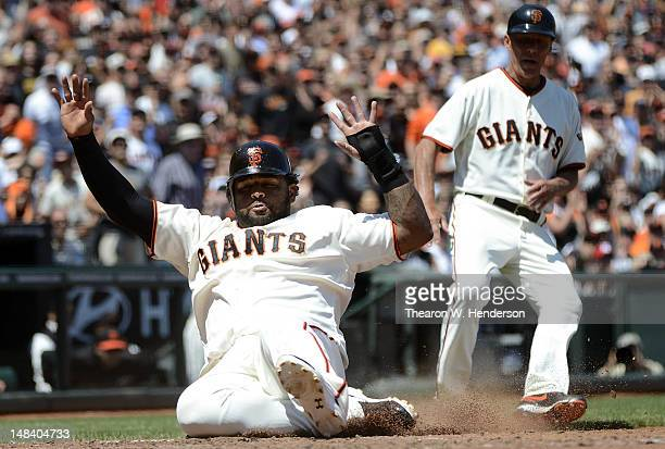 Pablo Sandoval of the San Francisco Giants slides in safe at home scoring on a Buster Posey RBI single as third base coach Tim Flannery looks on in...