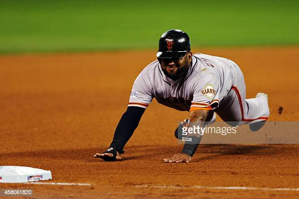 Pablo Sandoval of the San Francisco Giants slides into third base in the fourth inning against the Kansas City Royals during Game Seven of the 2014...