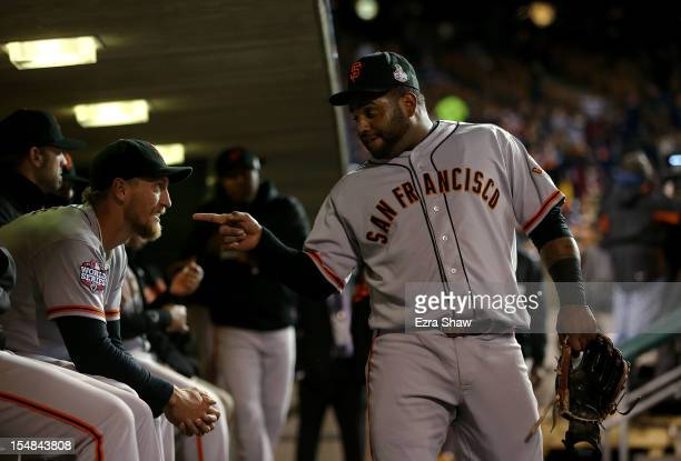 Pablo Sandoval of the San Francisco Giants talks with teammate Hunter Pence in the dugout prior to Game Three of the Major League Baseball World...