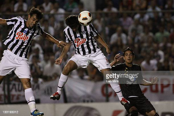 Pablo Velazquez and Gustavo Mencia from Libertad fights for the ball with Norberto Araujo from Liga Universitaria de Quito during a match between...