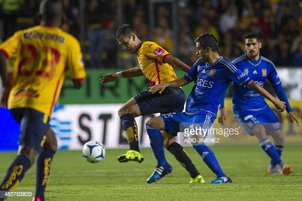 Pablo Velazquez of Morelia vies for the ball with Alonso Zamora of Tigres during their Mexican Apertura 2015 tournament football match at the Jose...