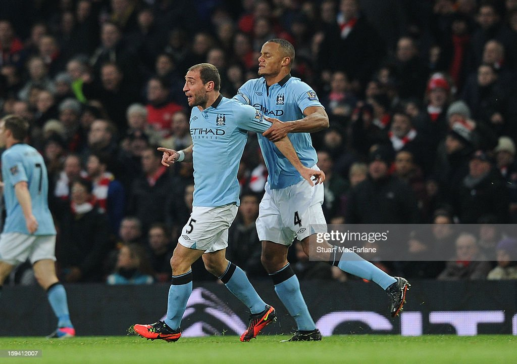 Pablo Zabaleta is held back by Man City captain Vincent Kompany after a challenge from Arsenal's Lukas Podolski during the Barclays Premier League match between Arsenal and Manchester City at Emirates Stadium on January 13, 2013 in London, England.