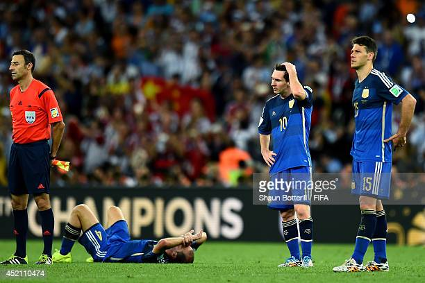 Pablo Zabaleta Lionel Messi and Martin Demichelis of Argentina react after the 01 defeat in the 2014 FIFA World Cup Brazil Final match between...