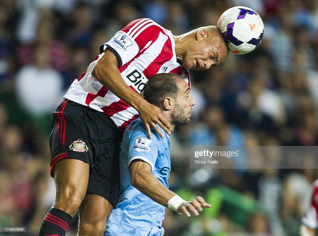 Pablo Zabaleta (R) of Manchester City and Wes Brown of Sunderland jump for the ball during the Barclays Asia Trophy Final match between Manchester City and Sunderland at Hong Kong Stadium on July 27, 2013 in So Kon Po, Hong Kong.