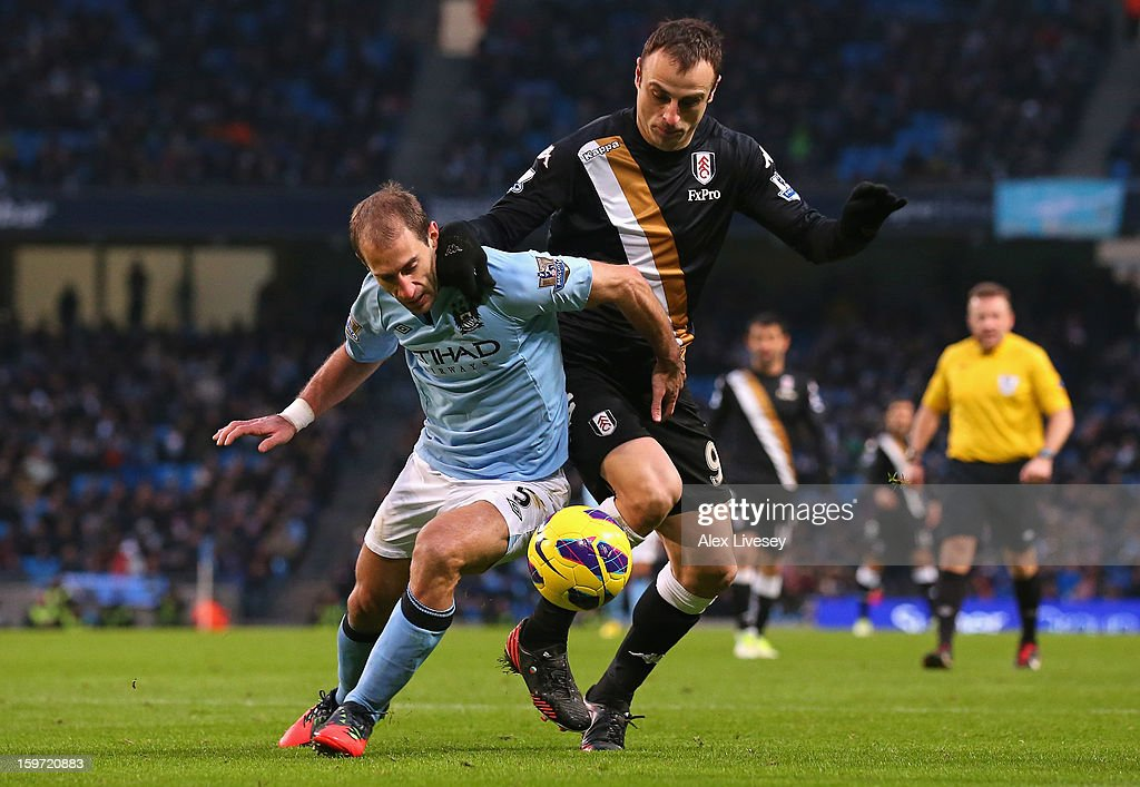 Pablo Zabaleta of Manchester City challenges Dimitar Berbatov of Fulham during the Barclays Premier League match between Manchester City and Fulham at Etihad Stadium on January 19, 2013 in Manchester, England.