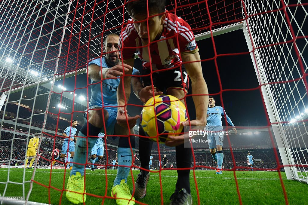 Pablo Zabaleta of Manchester City grabs the ball off a startled Santiago Vergini of Sunderland to complete his 'pregnant' celebration after scoring during the Barclays Premier League match between Sunderland and Manchester City at Stadium of Light on December 3, 2014 in Sunderland, England.