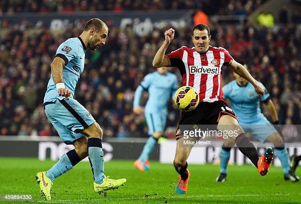 Pablo Zabaleta of Manchester City scores his team's third goal as John O'Shea of Sunderland closses in during the Barclays Premier League match...