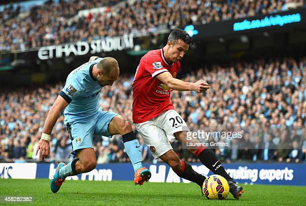 Pablo Zabaleta of Manchester City tackles Robin van Persie of Manchester United during the Barclays Premier League match between Manchester City and...