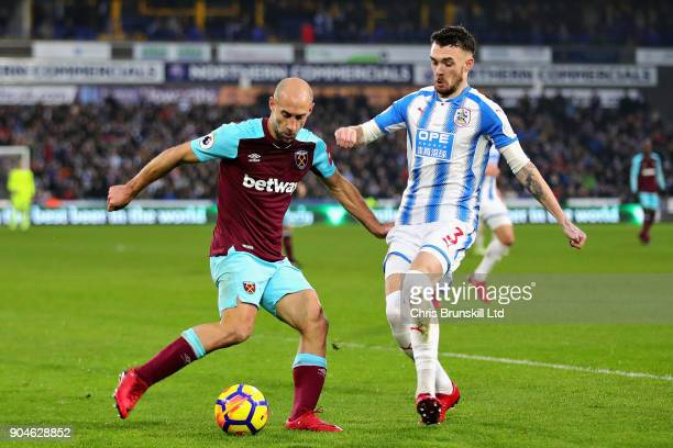 Pablo Zabaleta of West Ham United clears the ball from Scott Malone of Huddersfield Town during the Premier League match between Huddersfield Town...