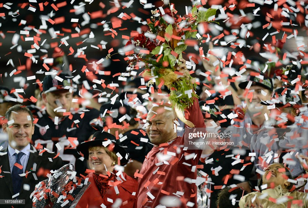 Pac-12 Commisioner Larry Scott (L) and Head Coach David Shaw of the Stanford Cardinal holding a bouque of red roses gets showered with confetti after the Cardinals defeated the UCLA Bruins 27-24 in the Pac-12 Championship Game at Stanford Stadium on November 30, 2012 in Stanford, California.
