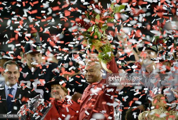 Pac12 Commisioner Larry Scott and Head Coach David Shaw of the Stanford Cardinal holding a bouque of red roses gets showered with confetti after the...