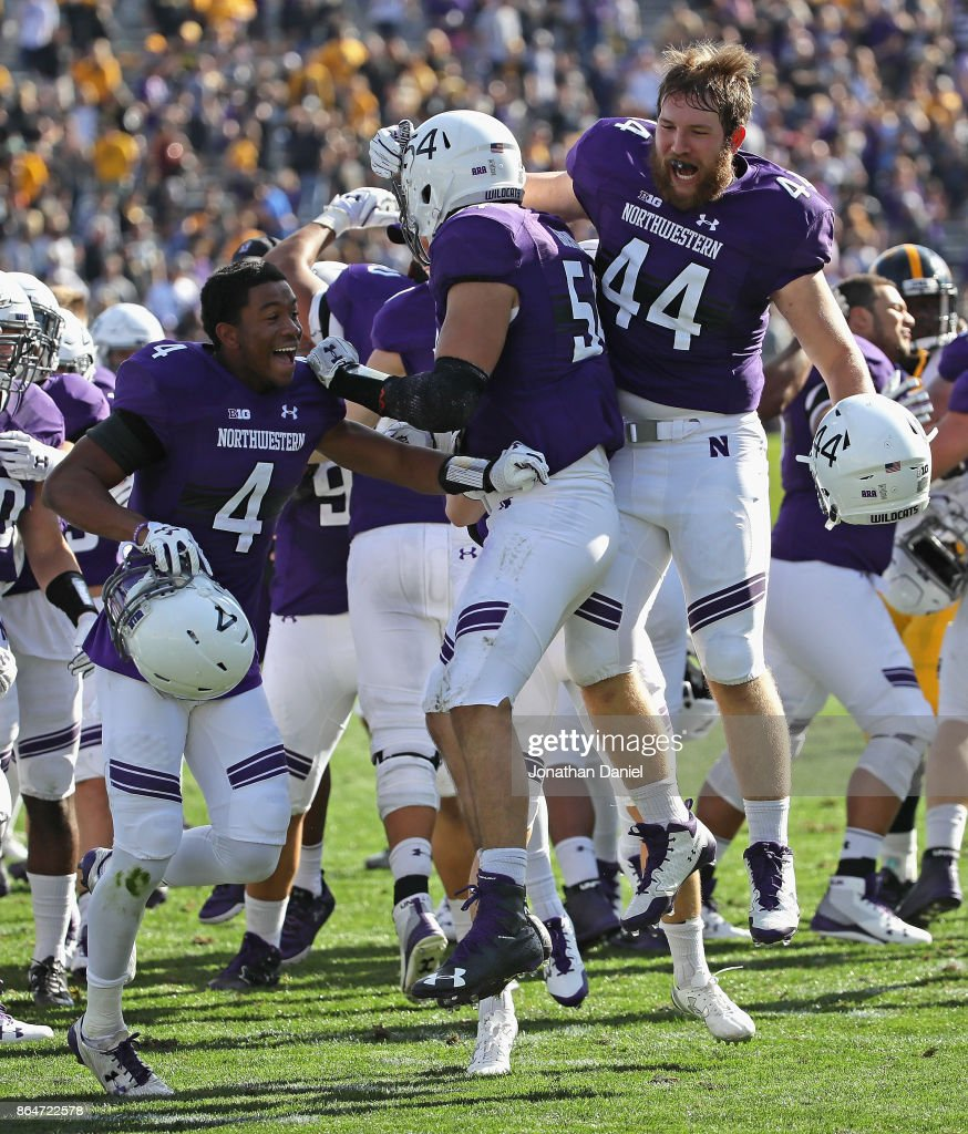 JR Pace #4, Trent Goens #54 and James Prather #44 of the Northwestern Wildcats celebrate a win over the Iowa Hawkeyes at Ryan Field on October 21, 2017 in Evanston, Illinois. Northwestern defeated Iowa 17-10 in overtime.