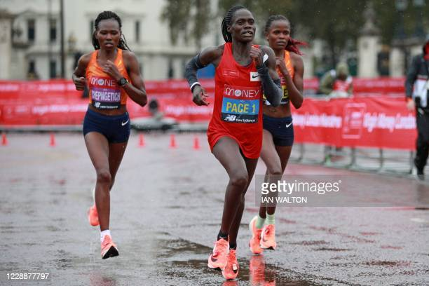 A pacemaker leads the two leaders Kenya's Ruth Chepngetich and Kenya's Brigid Kosgei in the women's race of the 2020 London Marathon in central...