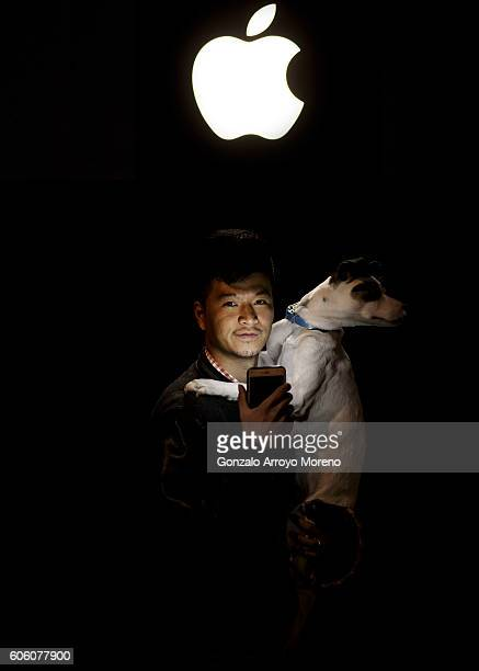 Pacheng Chen from China poses for a picture with his dog Jamon as he illuminates himself with his mobile phone at Puerta del Sol Apple Store facade...
