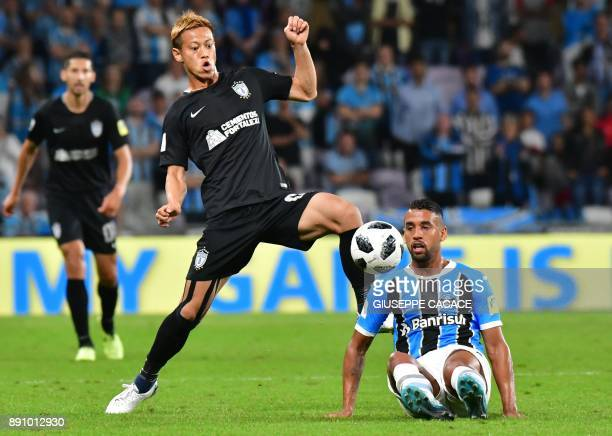 CF Pachuca's midfielder Keisuke Honda of Japan fights for the ball against Gremio FBPA's midfielder Michel of Brazil during the first semifinal of...