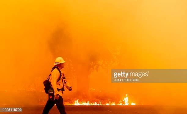 Pacific Gas and Electric firefighter walks down a road as flames approach in Fairfield, California during the LNU Lightning Complex fire on August...