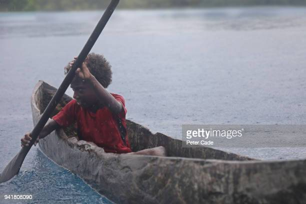 Pacific Island child in homemade canoe in the rain