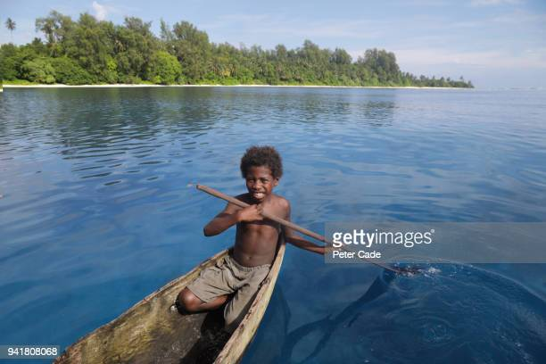 Pacific Island child in homemade canoe