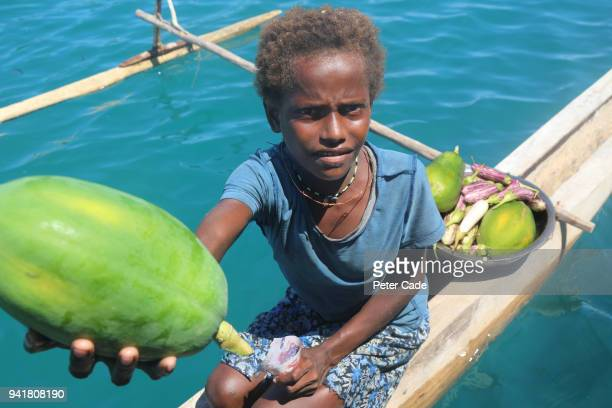 Pacific Island child selling fruit from canoe