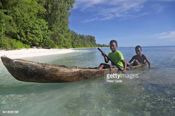 Pacific Island children in homemade canoe