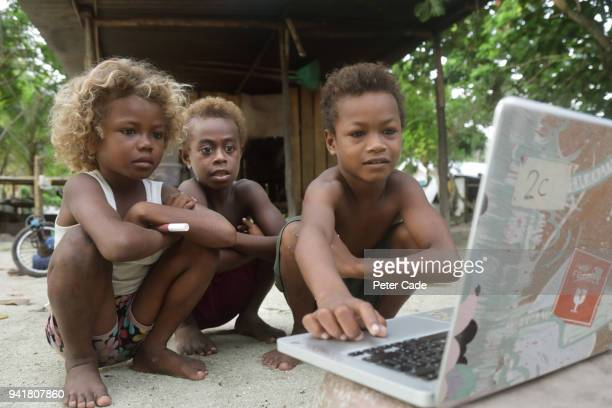 Pacific island children looking at laptop