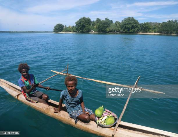 Pacific Island children selling fruit from canoe