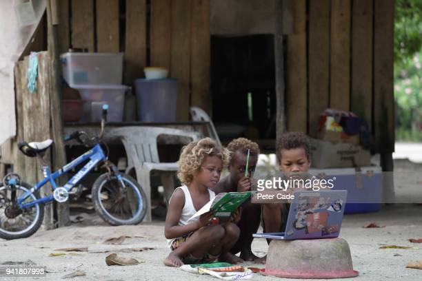 Pacific island children working on laptop