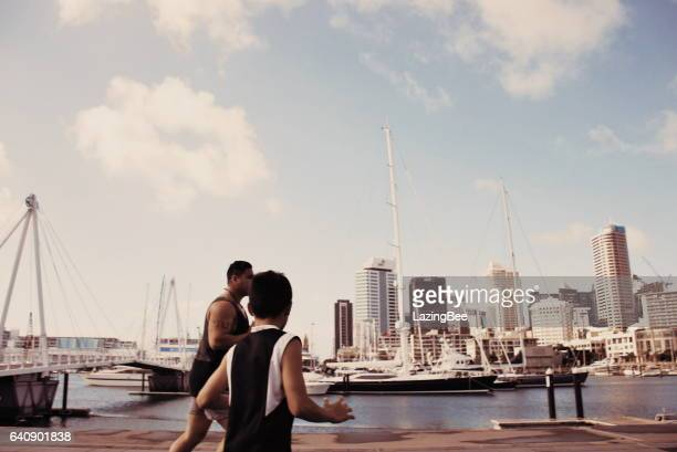 pacific island man and boy plays rugby against a cityscape harbour - waitemata harbor stock photos and pictures
