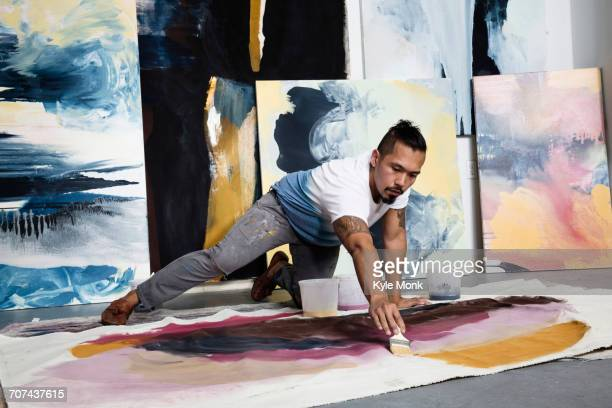 pacific islander artist kneeling on floor painting on canvas - costa mesa stock photos and pictures