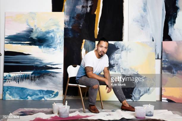 pacific islander artist sitting with paintings - artist stock pictures, royalty-free photos & images