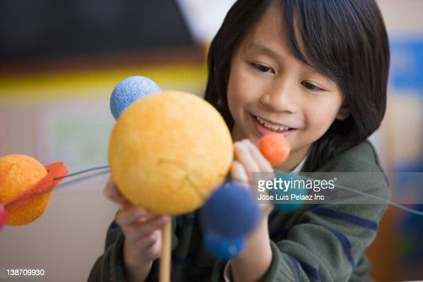 pacific islander boy making planet model in classroom - solar system stock photos and pictures