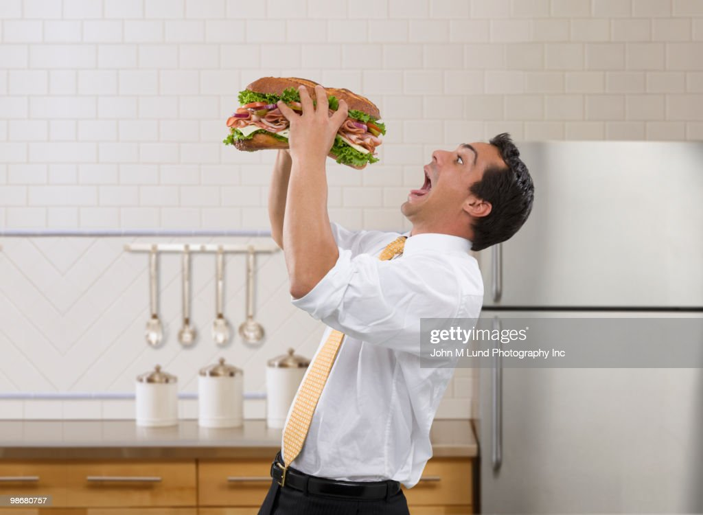Pacific Islander businessman eating large sandwich : Stock Photo