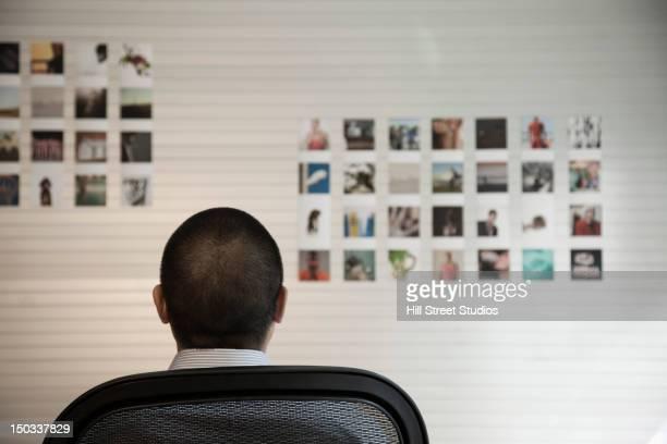 Pacific Islander Geschäftsmann auf der Suche auf Bilder an der Wand