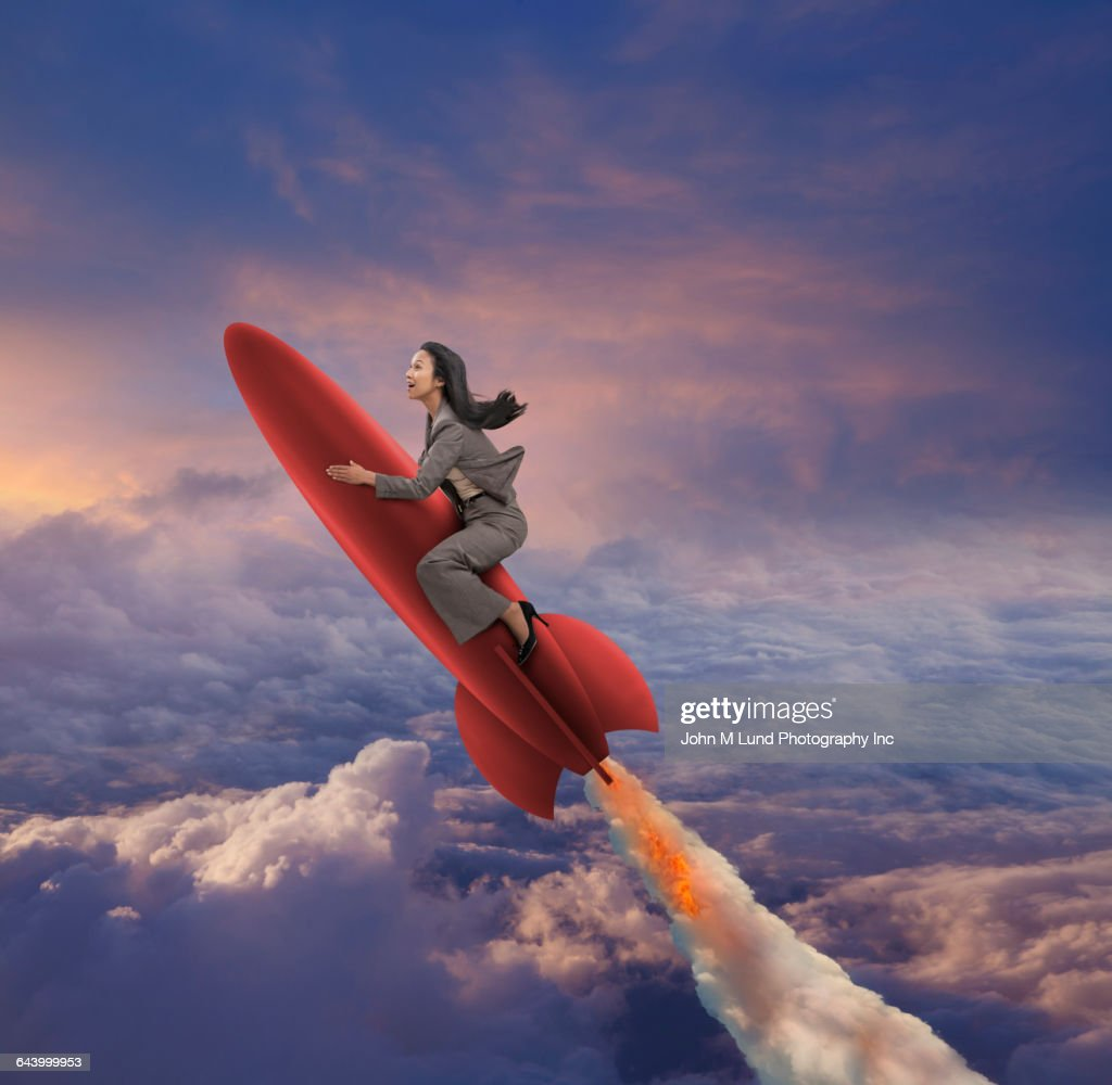 Pacific Islander businesswoman riding rocket in sky : Stock Photo
