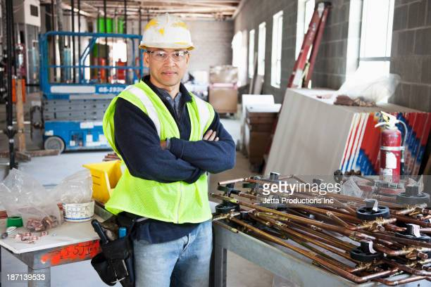 Pacific Islander construction worker with arms crossed