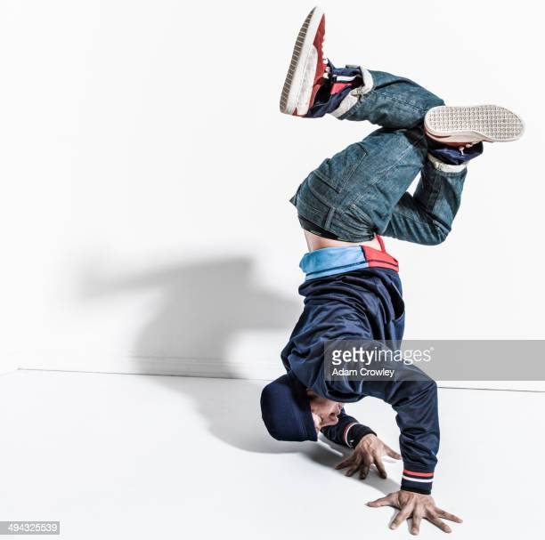pacific islander dancer casting shadows on wall - breakdancing stock photos and pictures