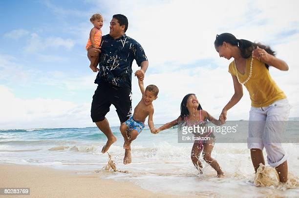 Pacific Islander family jumping in ocean surf