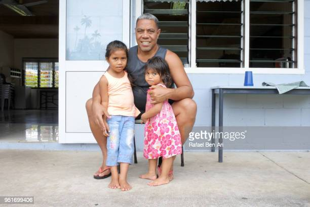 Pacific Islander father hugs his two little daughters