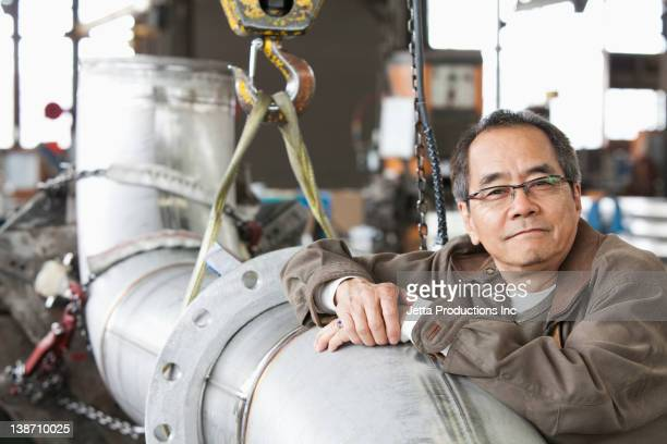 Pacific Islander leaning on pipe in factory