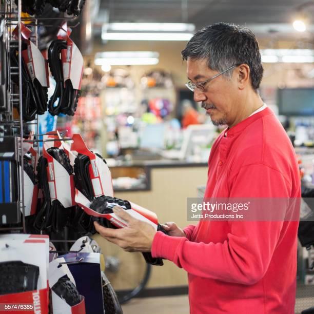 Pacific Islander man examining tire in bicycle shop