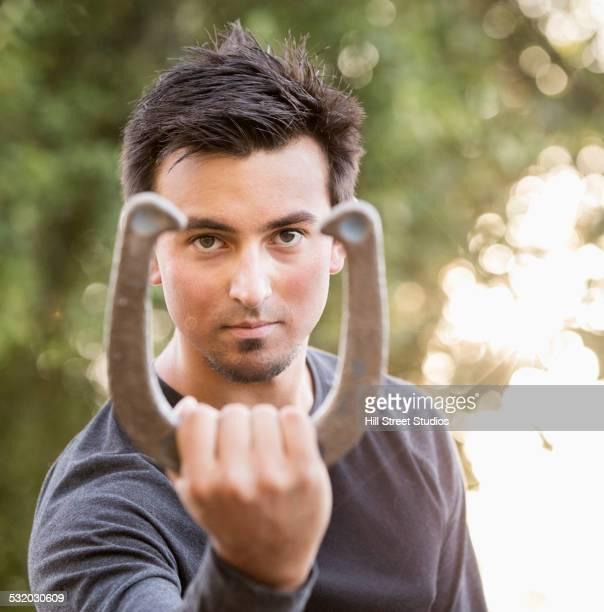 Pacific Islander man holding horseshoe outdoors