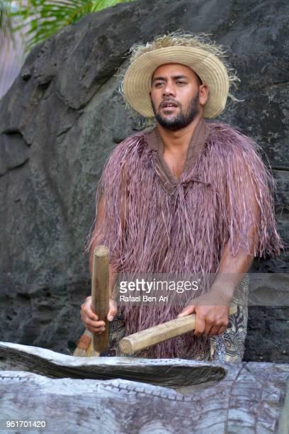 pacific islander man plays music on a large wooden log pate drum instrument in rarotonga cook islands - rafael ben ari bildbanksfoton och bilder